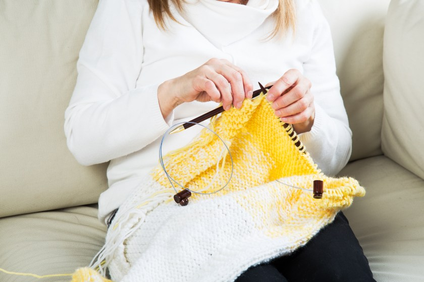 A woman is seen sitting on a couch knitting a yellow and white garment with straight knitting needles from My Two Ladies