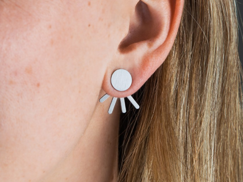 A close up of a girl's ear shows her wearing Trifecta convertible stainless steel earrings from Days of August