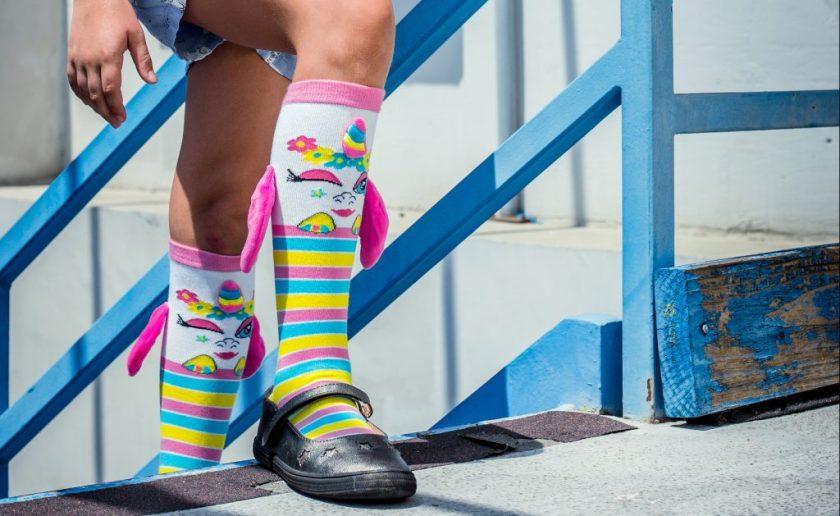 A little girl is seen wearing rainbow knee-high character socks from MooshWalks