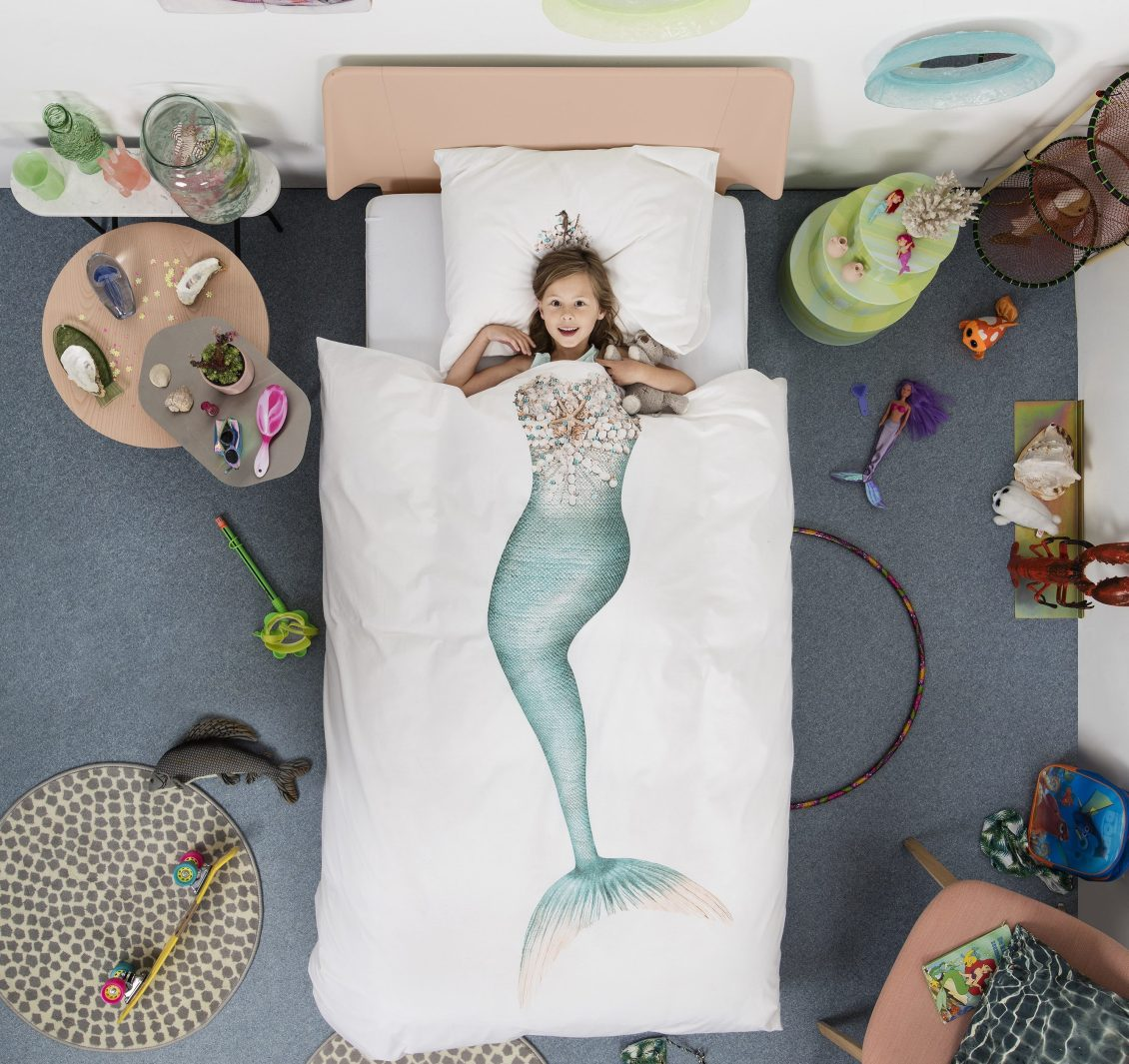 A little girl is seen laying in bed under a Mermaid duvet cover from Snurk Living
