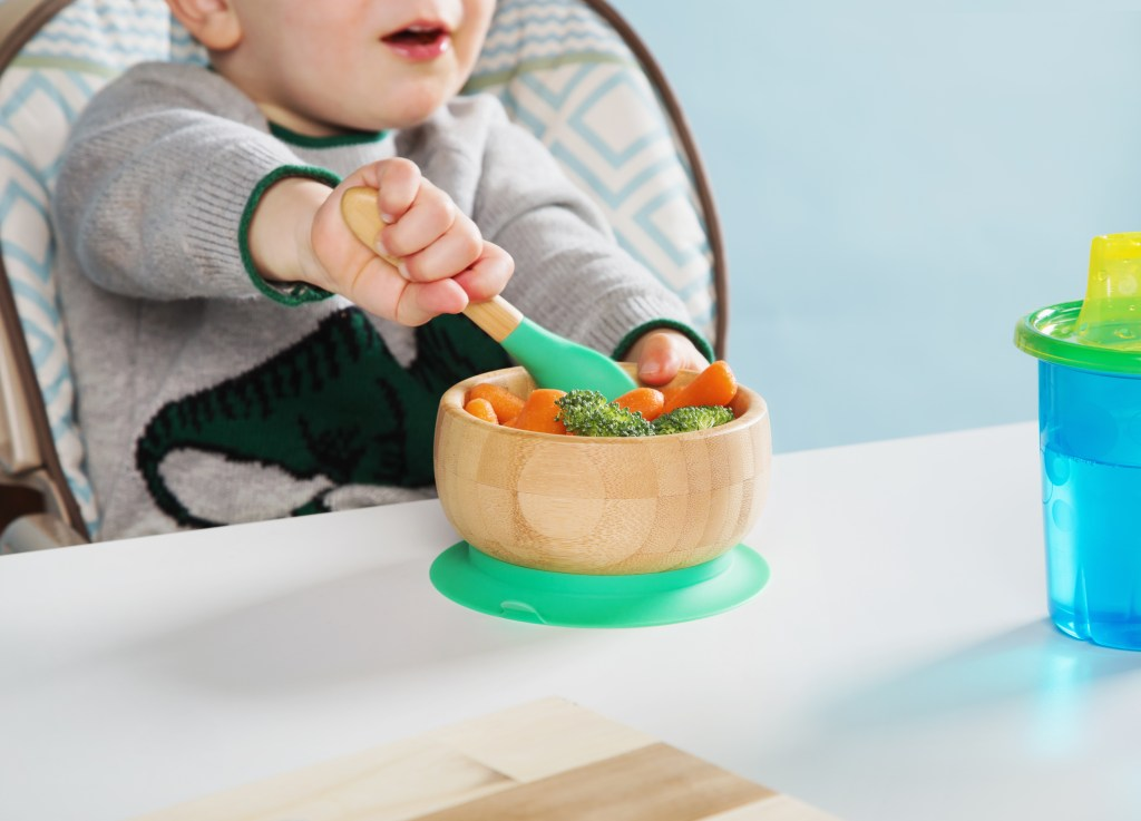 A toddler is seen scooping broccoli & carrots out of a bamboo suction bowl from Avanchy