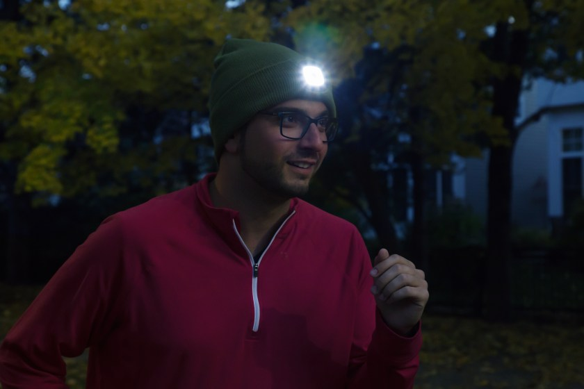 A man running at night wearing a Night Scout lighted beanie