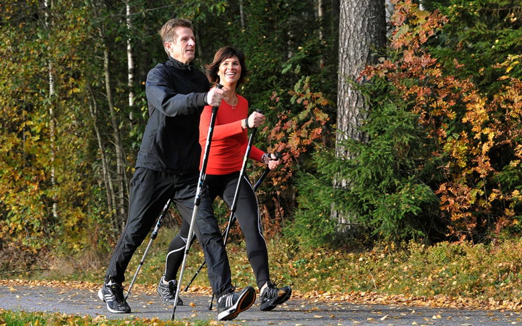 Two people are seen speedwalking on a path in the fall using BungyPump walking sticks