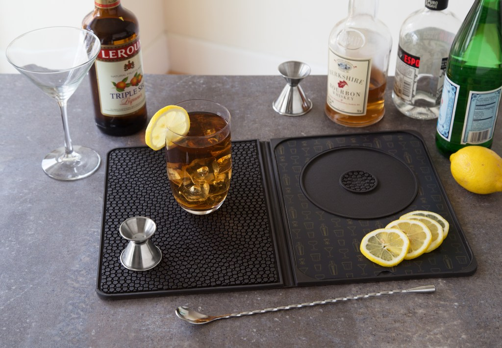 A cocktail sits expertly made on a multi-use cocktail bar mat from Talisman Designs amidst all the ingredients