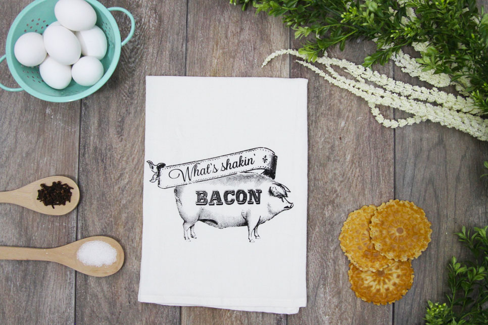 "A white ""What's Shakin' Bacon"" kitchen towel from The Coin Laundry lays on a countertop next to eggs and spices"