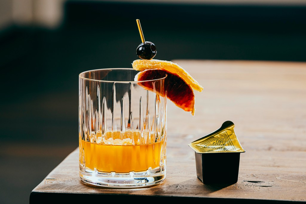 An old fashioned cocktail sits on a table next to an Herb & Lou's cocktail-infused ice cube
