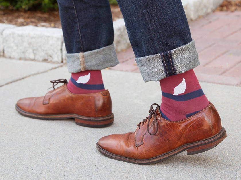 A man is seen walking wearing brown loafers and maroon pima cotton socks from Soxfords
