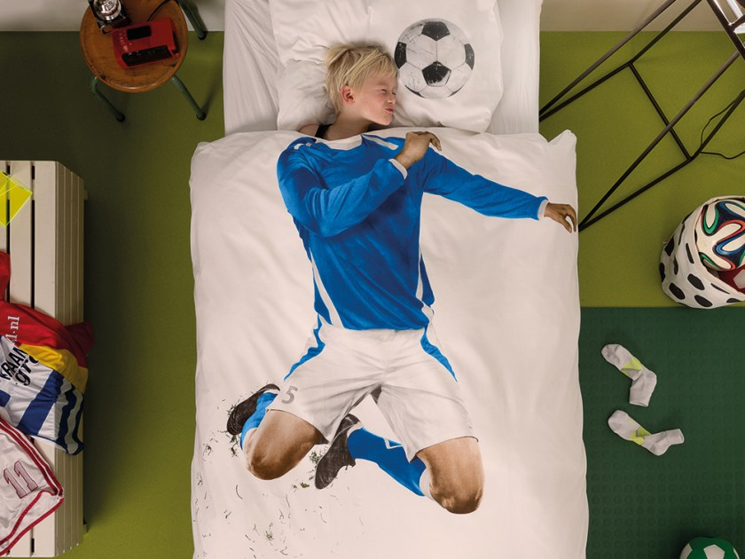 A young boy is seen sleeping in bed covered with a Snurk Living duvet set made to look like a soccer player in a blue jersey