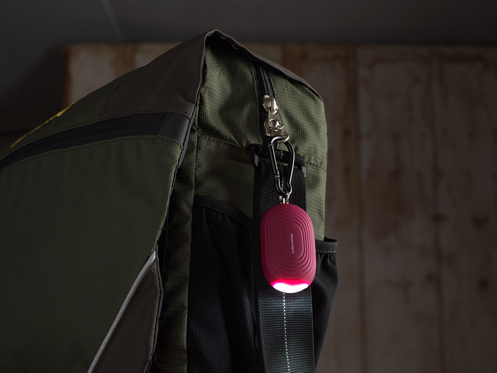 A red iMaxAlarm LED personal security alarm is seen clipped to an olive backpack