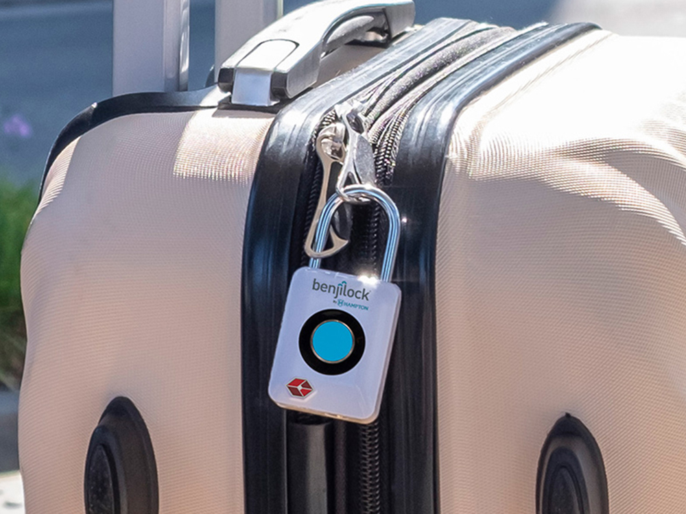 A TSA-approved fingerprint travel lock from Benjilock is seem clipped to a suitecase