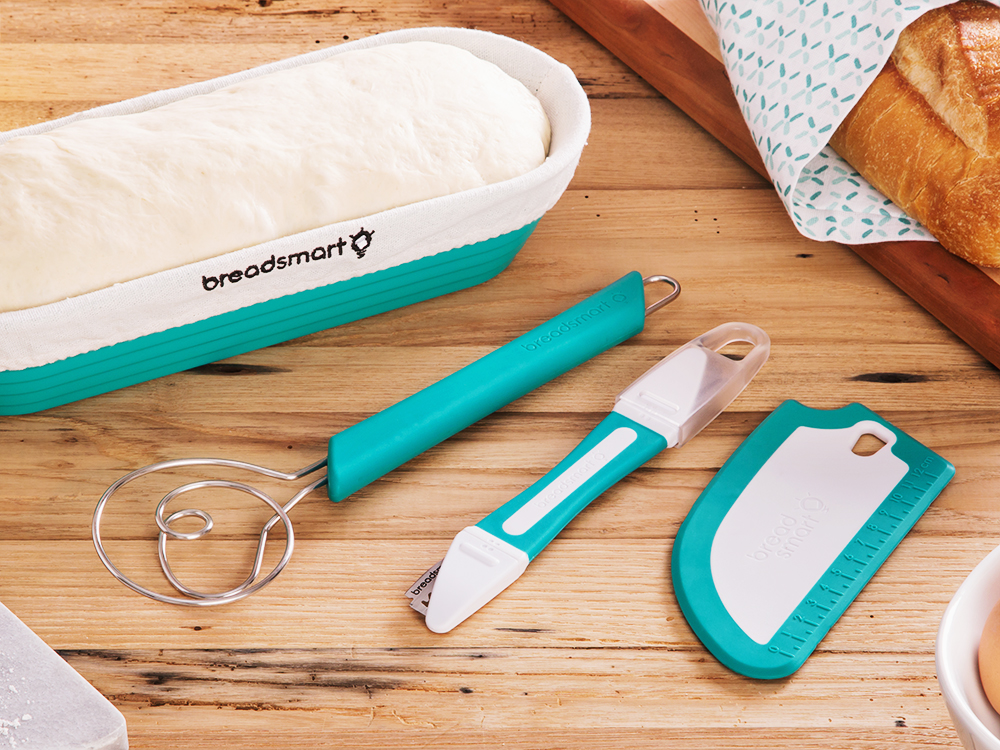 A bread making kit from BreadSmart on a wooden counter. A teal proofing basket, a teal whish, a teal lame, and a teal bench scraper.
