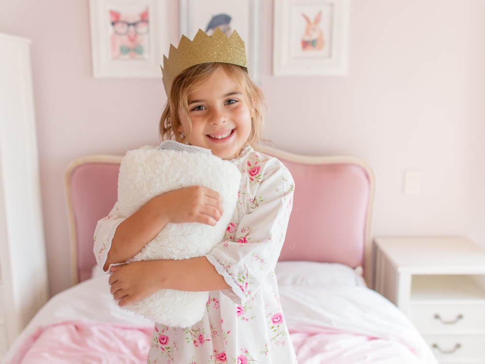 A little girl is seen standing on her bed wearing a crown and lugging her Dream Pillow