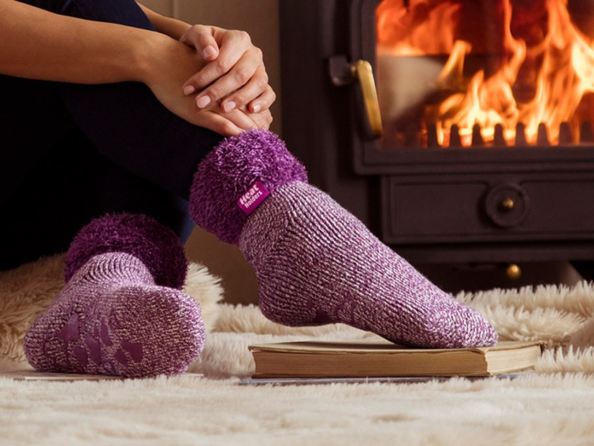 A woman is seen lounging by the fire wearing pink brushed thermal lounge socks from Heat Holders