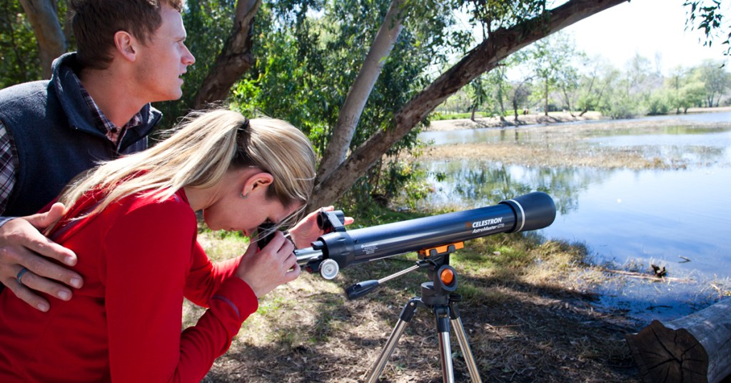 A couple is seen on the edge of a lake using an AstroMaster LT telescope to look at nature