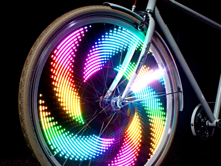 Brightly colored lights spin on the wheel of a bike thanks to MonkeyLectric monkey lights