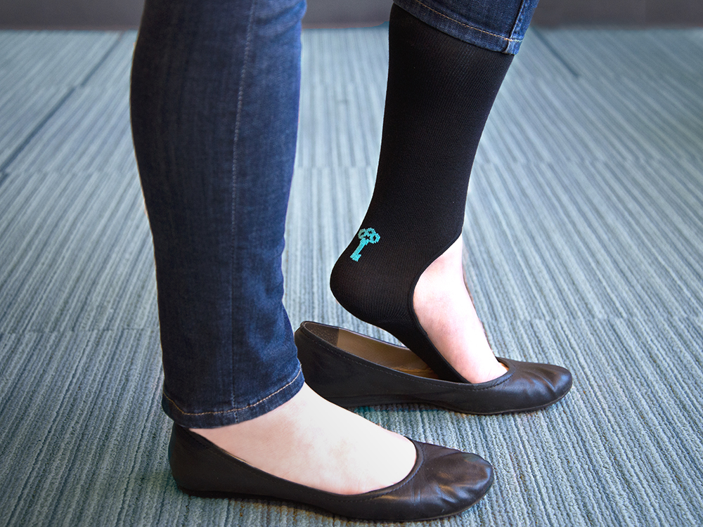 A woman is seen wearing jeans, black ballet flats and a pair of Keysocks no-show socks