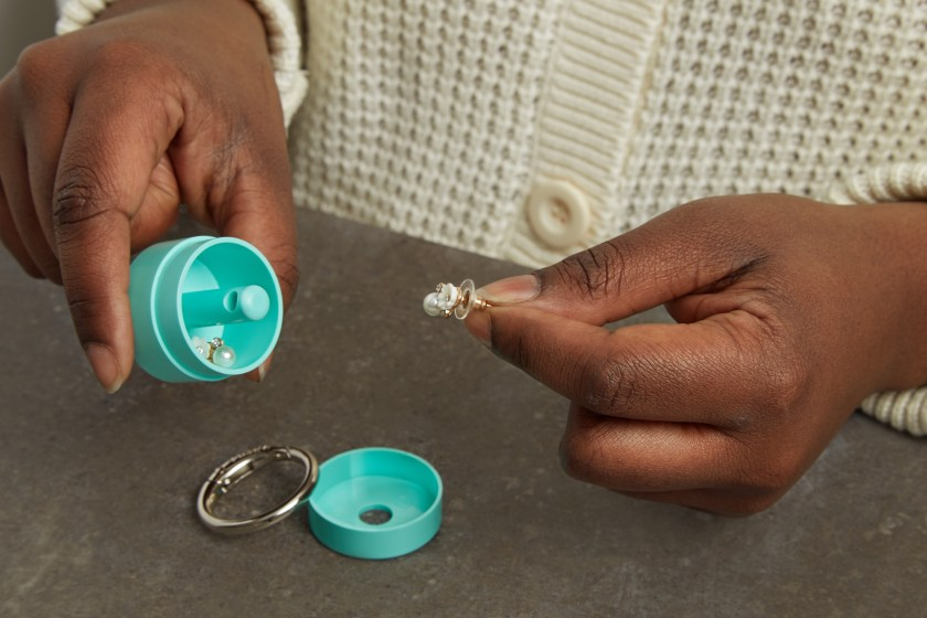 A woman is seen putting a pair of earrings into a teal Lion Latch keychain jewelry holder