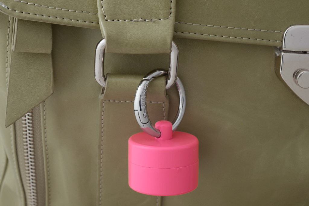 A pink Lion Latch keychain jewelry holder . is seen clipped to a beige bag