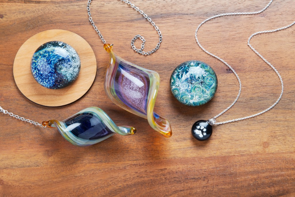 Two paperweights, two sun catchers and a pet memorial ashes glass necklace from TZ Glass by Tari Zarka lay on a table