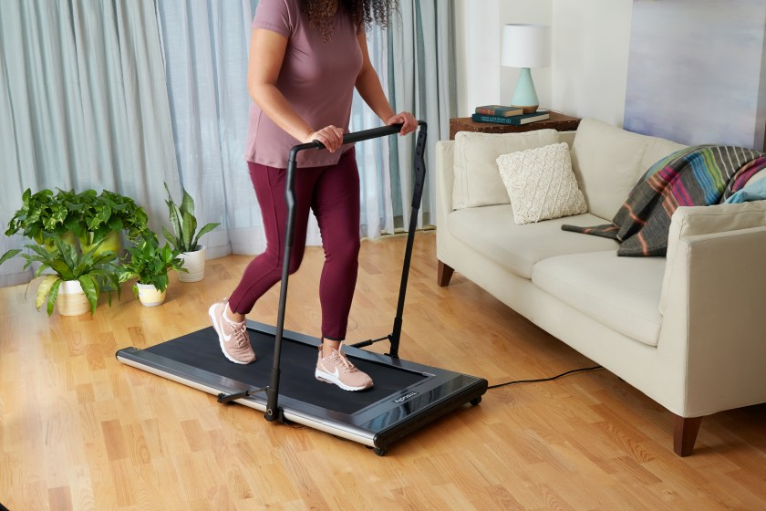 A woman is seen running on an ultra thin Treadly treadmill in her living room