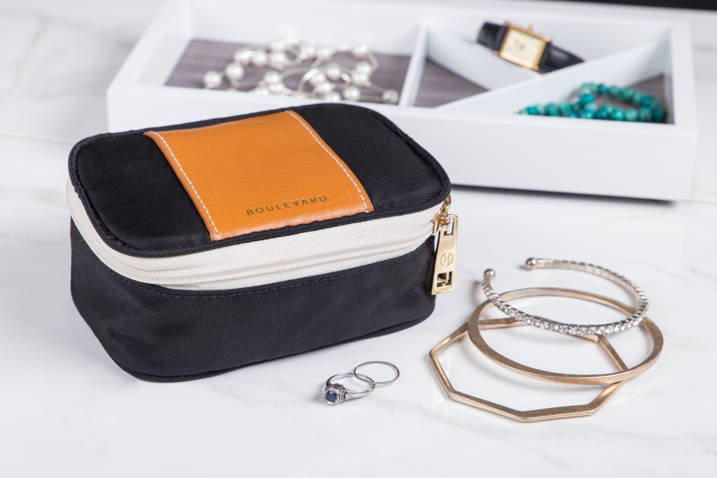 A black & tan tangle-free jewelry box from Boulevard sits next to a tray of jewelry