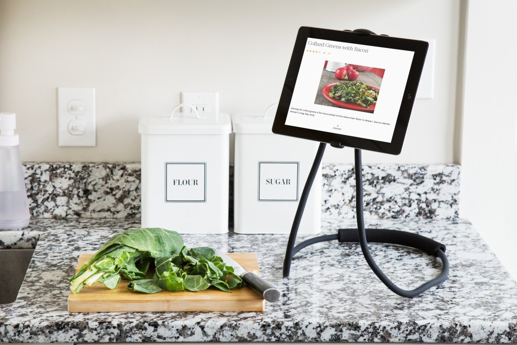 A tablet sits suspended in a wearable mobile device stand on a counter with a cooking recipe onscreen