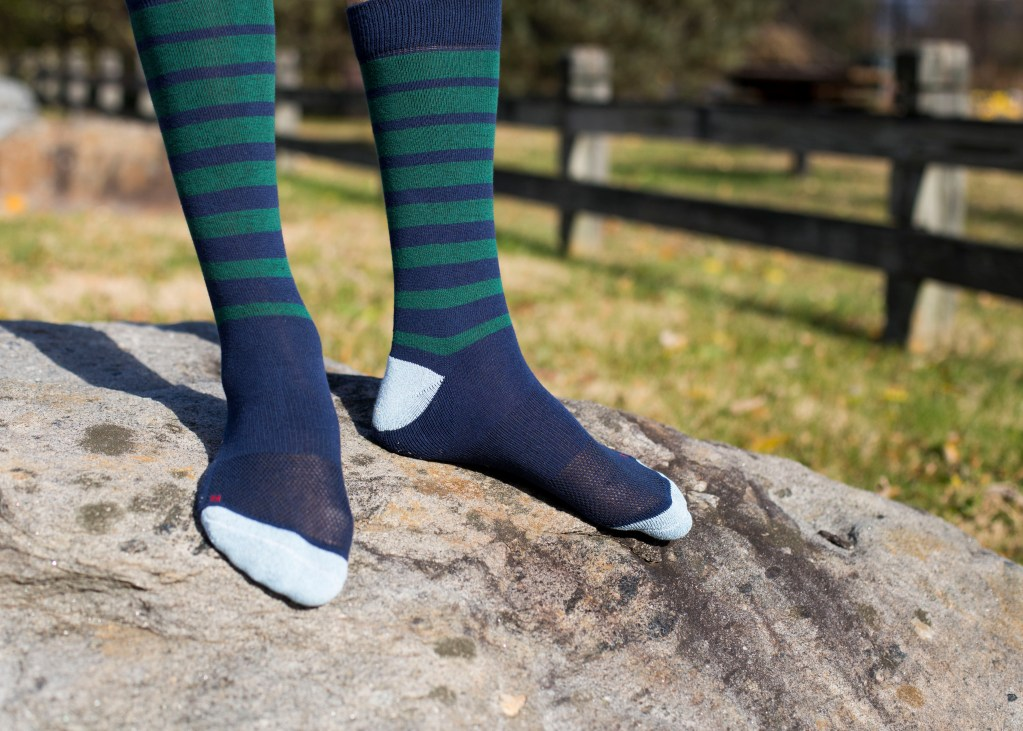 A person stands on a rock wearing blue and green striped socks from Proper Socks
