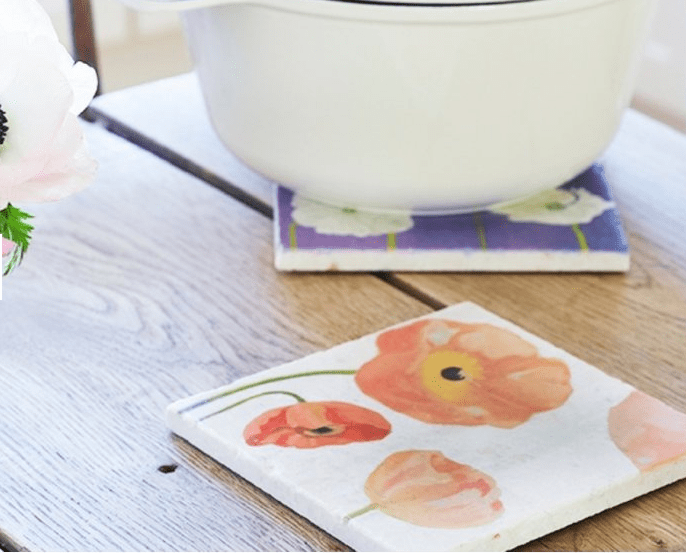 Colorful floral trivets from India & Purry by Jessica Hollander are seen on a kitchen table