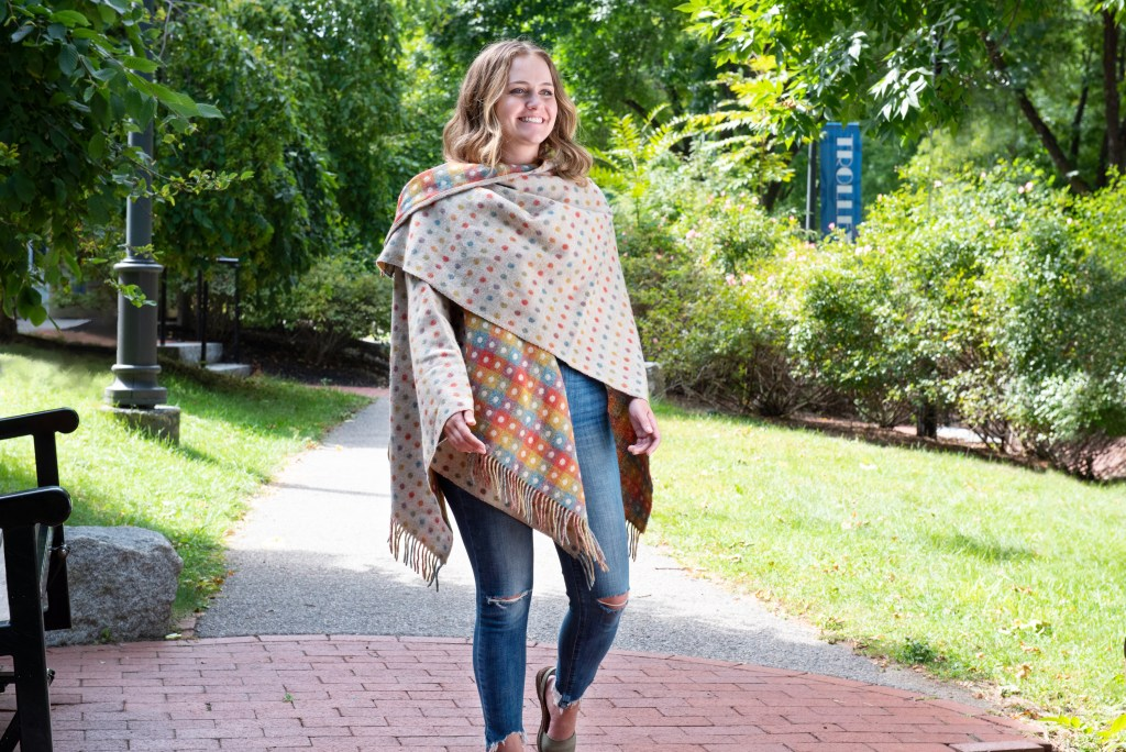 A woman is seen walking in a park wearing an Abraham Moon polka dot wool Ruana wrap