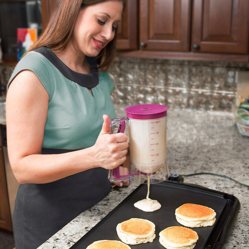A woman is seen using a KPKitchen portion control batter dispenser to dispense pancakes on a griddle
