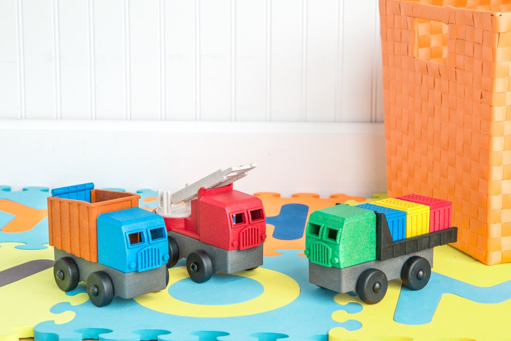 Three ecotruck fire truck toys from Luke's Toy Factory are seen in a playroom