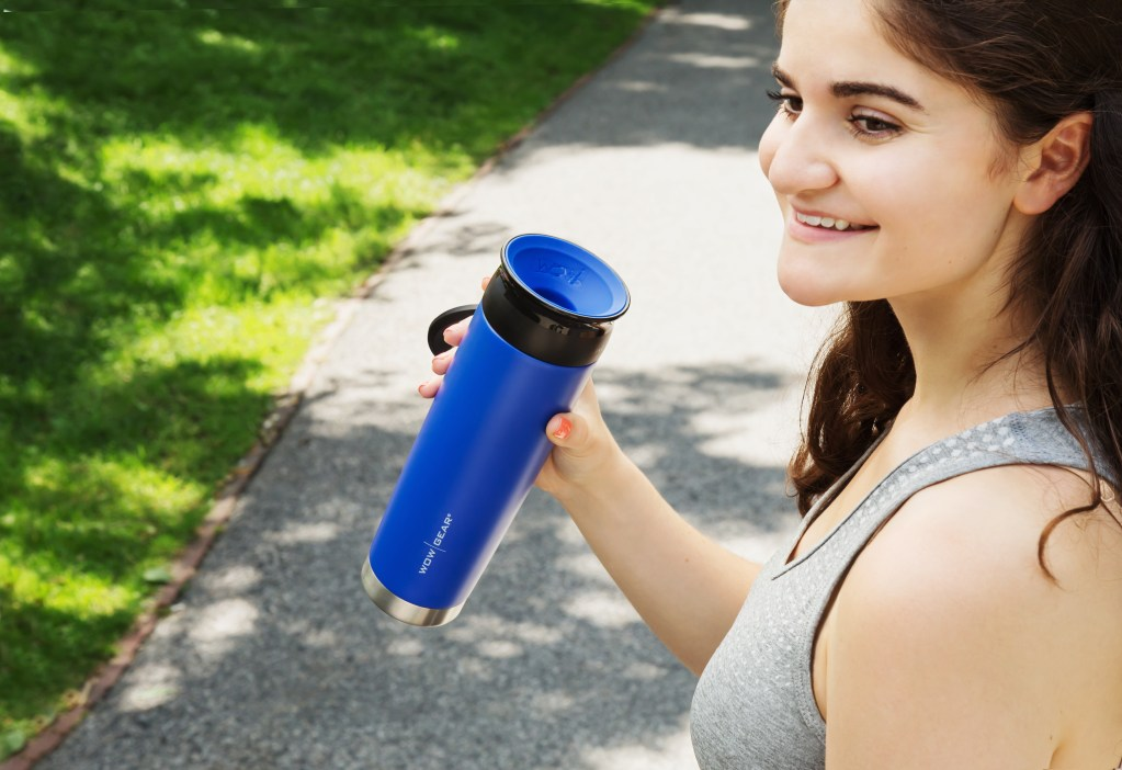A woman is seen in a park holding a blue 360-degree stainless steel water bottle from WOW Gear