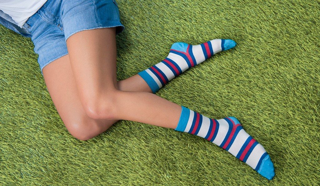 A woman is seen laying in the grass wearing a pair of red and blue striped organic cotton socks from Zkano