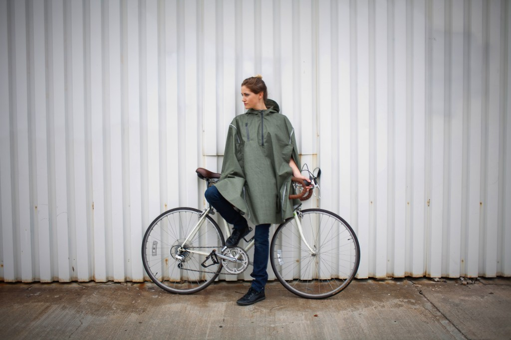 A woman is seen standing next to her bike wearing an olive green Cleverhood high-performance rain cape