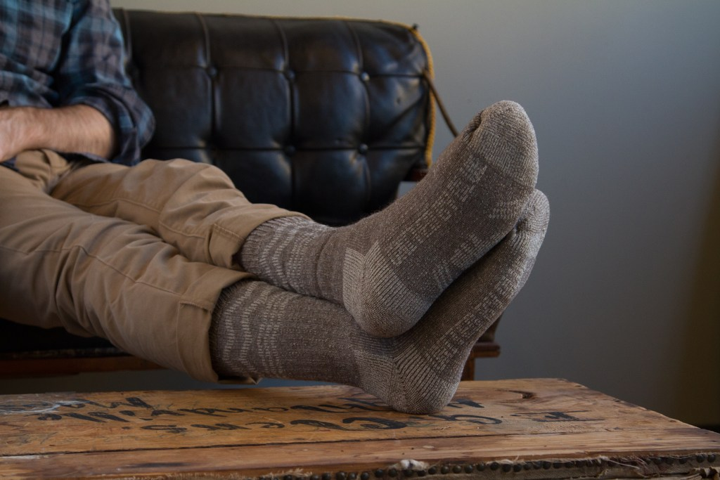 A man is seen lounging wearing a pair of bison down socks from United By Blue