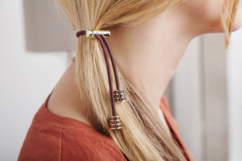 A blonde girl is seen with her hair pulled into a side ponytail using Pulleez crystal sliding hair ties