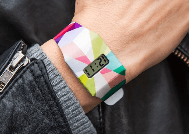 A person is seen wearing a multicolored geometric printed Tyvek paper watch from I Like Paper, the time reads 12:11