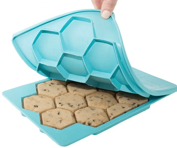 A teal cookie shaper from Shape + Store is seen with raw cookie dough in it