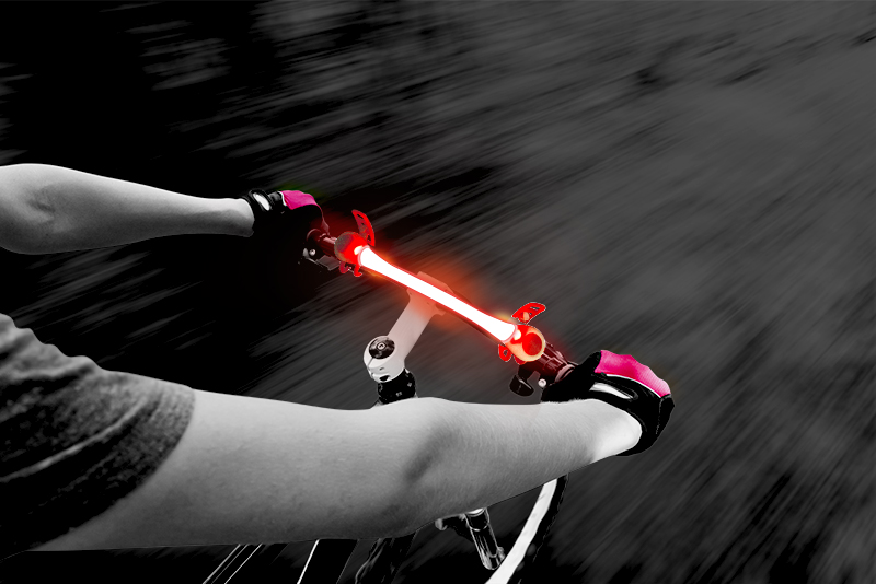 A person is seen riding their bike at night, the handle bar illuminated by 4id's PowerWrapz LED safety bands