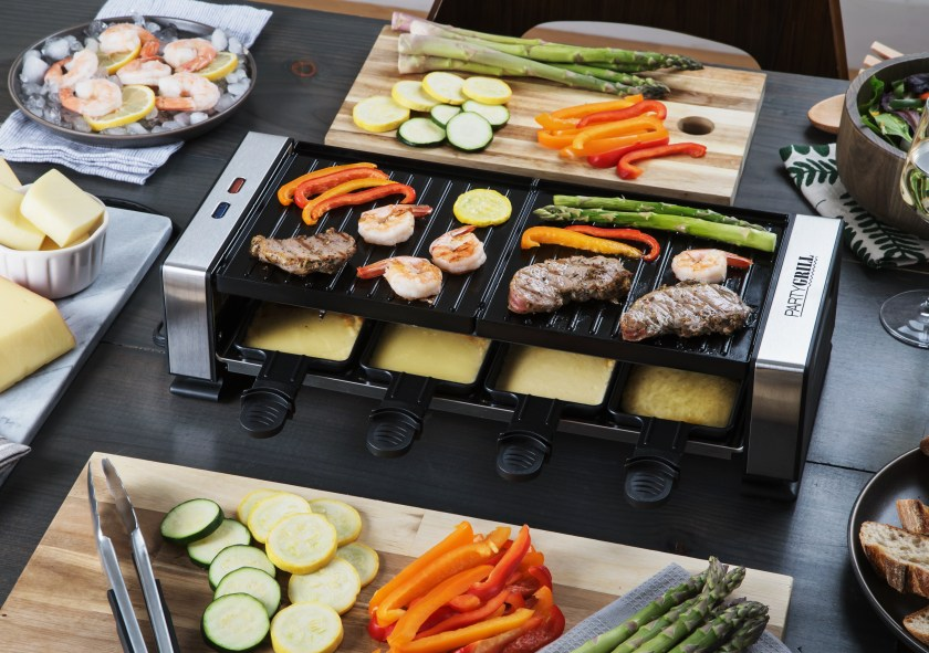 Veggies and meat are seen cooking on a grill top while cheese melts in the raclette from Party Grill