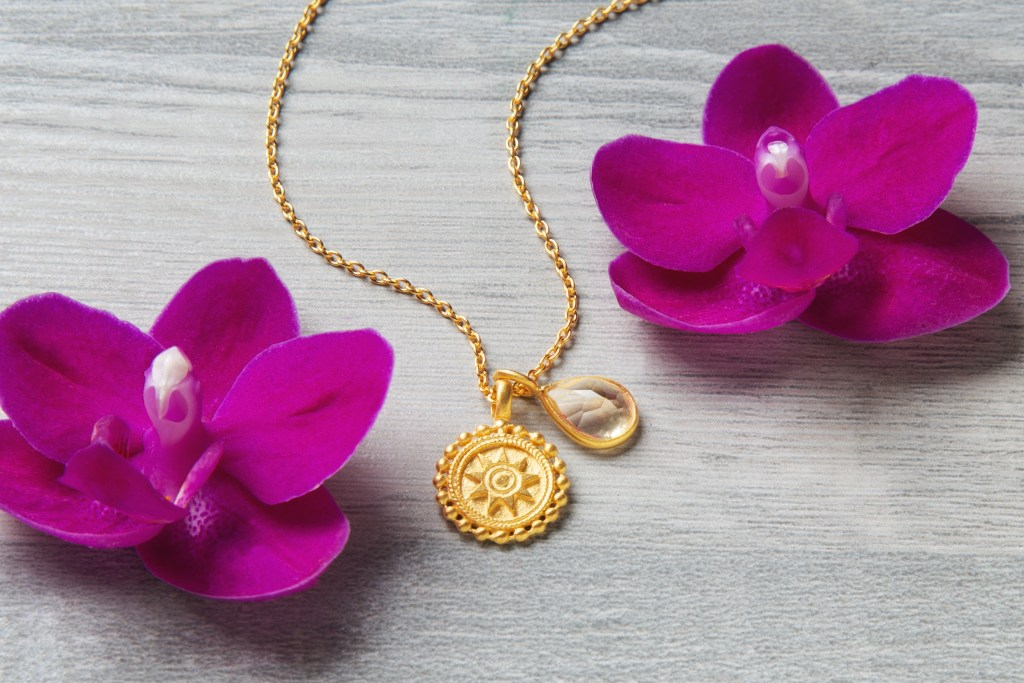 A gold birthstone Mandala necklace from Satya Jewelry lays next to two pink orchids