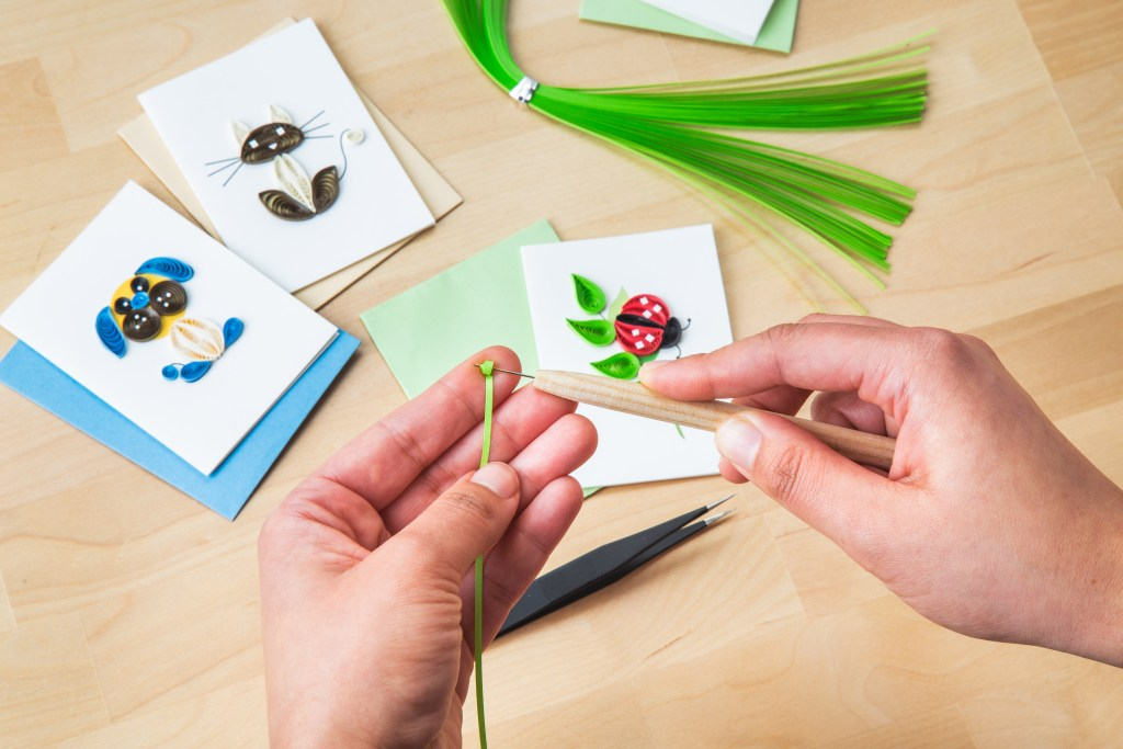 A person is seen quilling paper with a Quilling Cards beginner's kit, with a dog, cat and ladybug card in the background