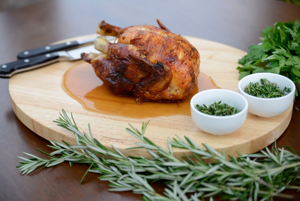 A whole roasted chicken surrounded by fresh herbs sits on a concave wooden carving board from Architec