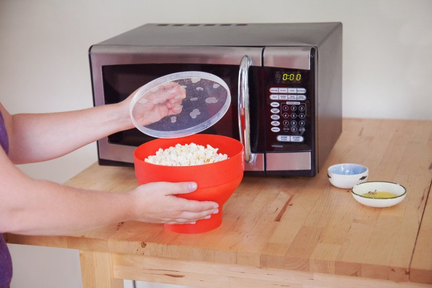 A person is seen opening a bowl of popcorn that has been popped in the microwave using Lékué's silicone popcorn maker