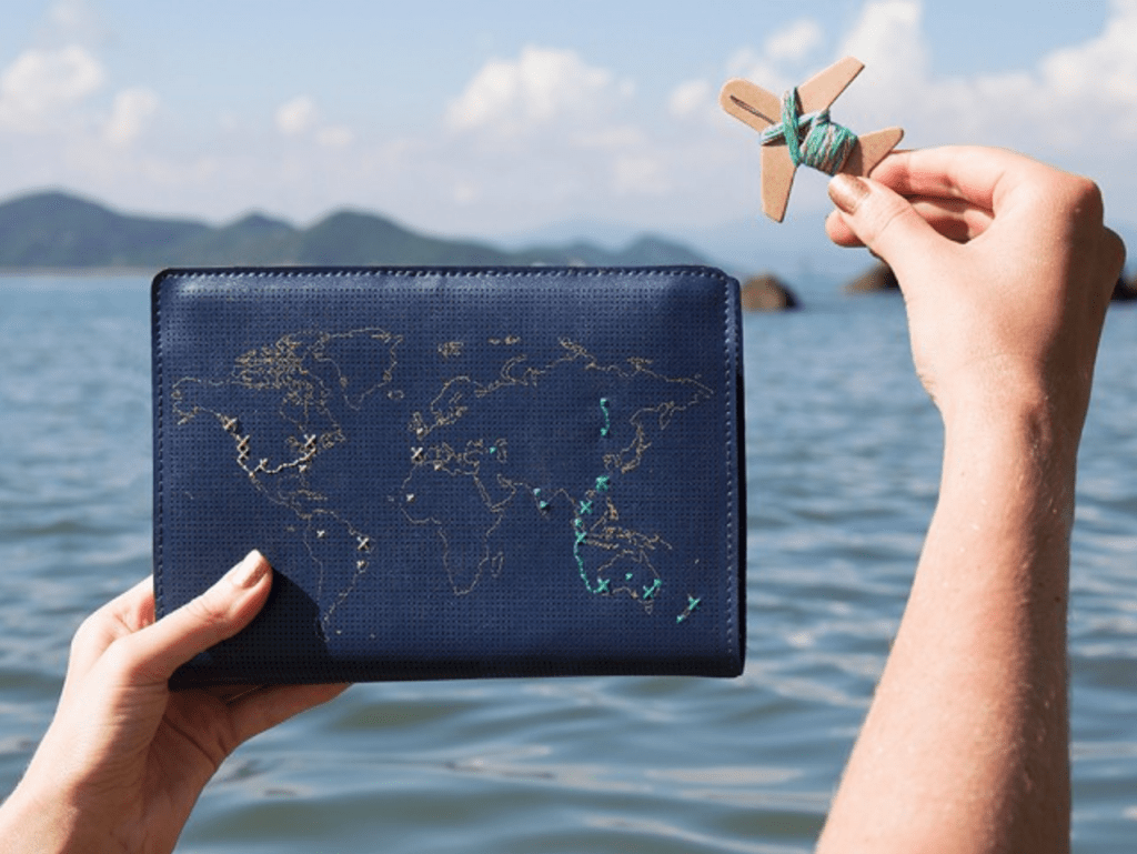 A navy leather notebook from Chasing Threads is seen stitched with places a person has traveled