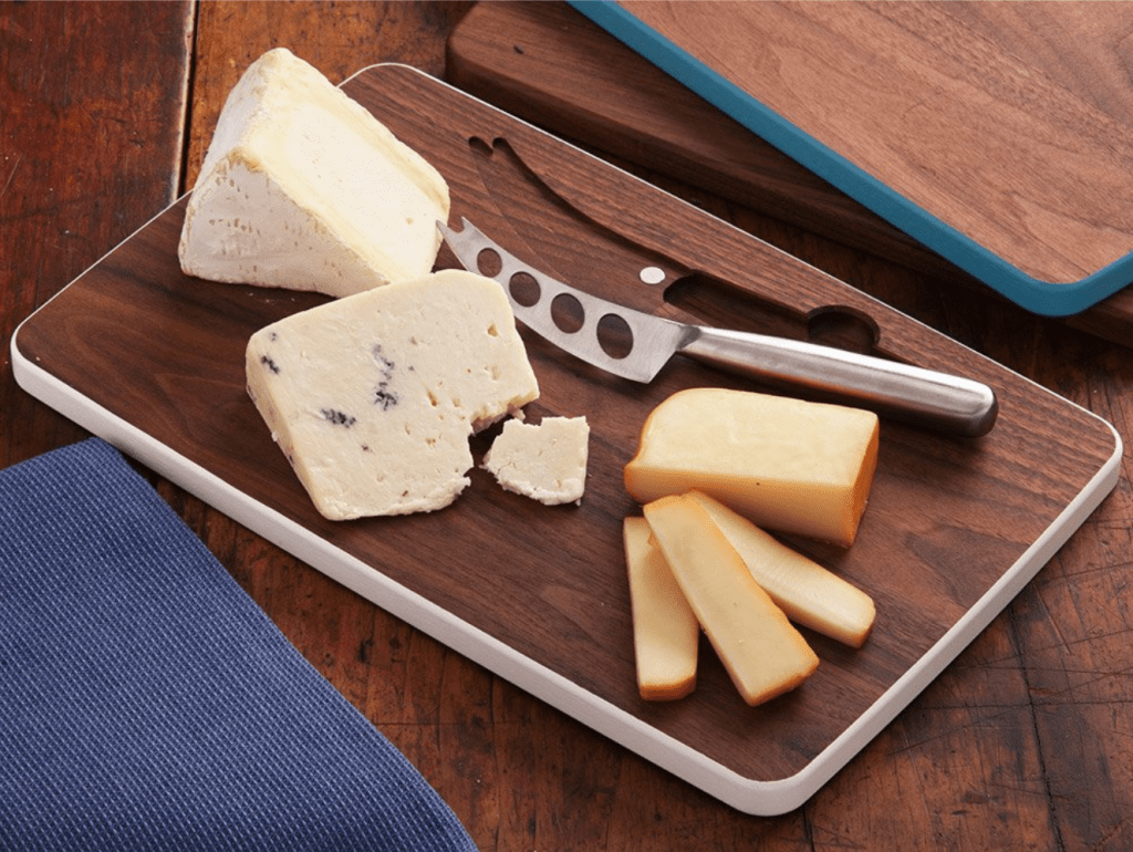 Wedges of cheese are sliced on a David Rasmussen cheese board and knife set