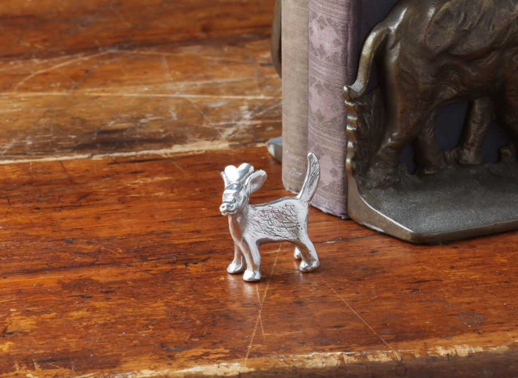 A dog love pewter sculpture from Tamara Hensick Designs sits on a desk