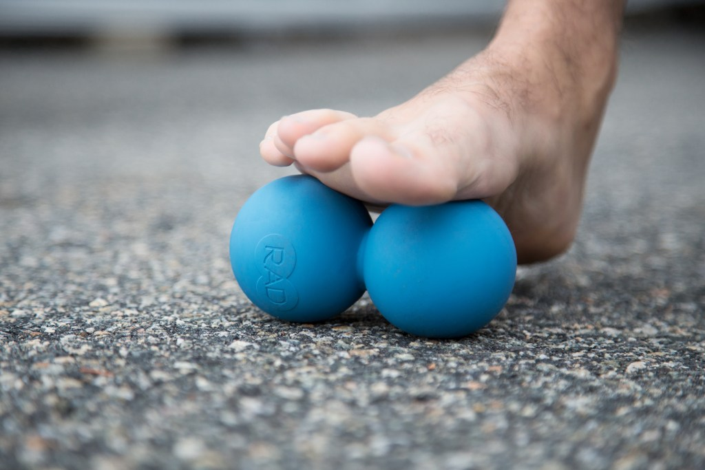 A person is seen rolling their toes using blue RAD massage roller balls