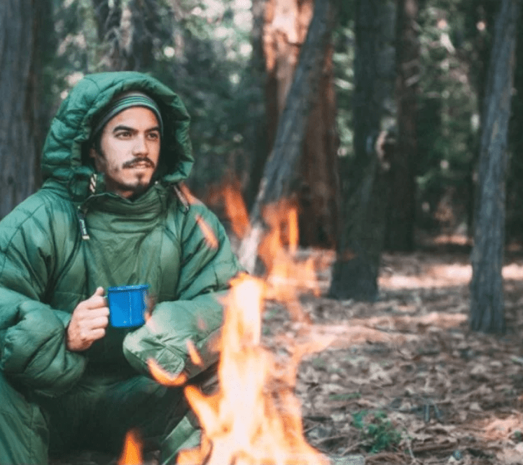 A man is seen sitting by the fire wearing a green Selk'bag wearable sleeping bag suit