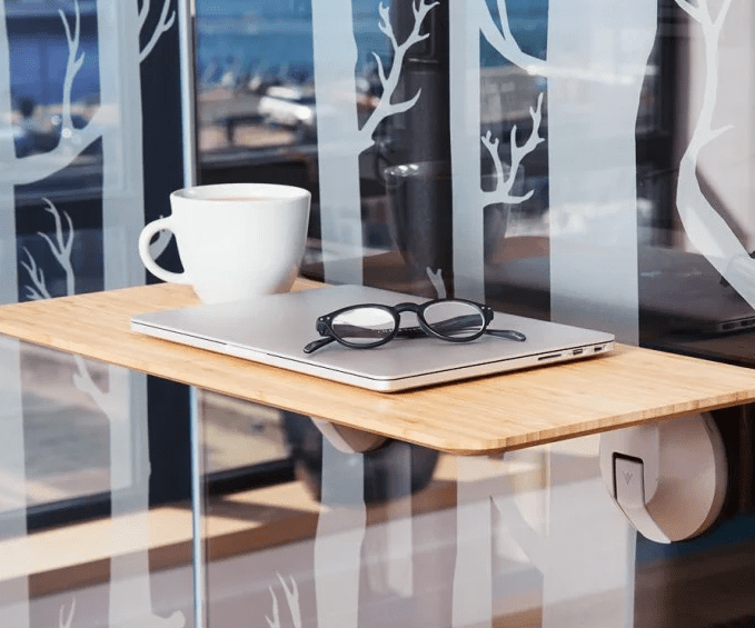 A coffee mug, glasses & a laptop are seen resting on a DeskView window-mounted standing desk